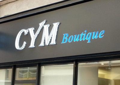 Vos enseignes à Lyon: Enseigne lumineuse avec caisson de façade et Drapeau double face à Lyon pour Cym Boutique (Lyon 69006) par SES (Grigny-Lyon)